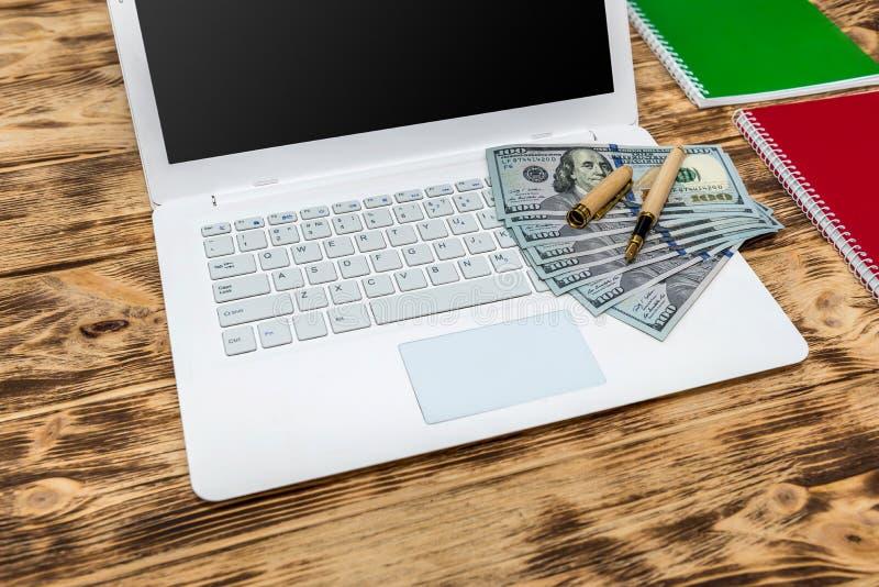 Bankbiljetten in dollar op pc-toetsenbord en leeg notepad royalty-vrije stock foto's