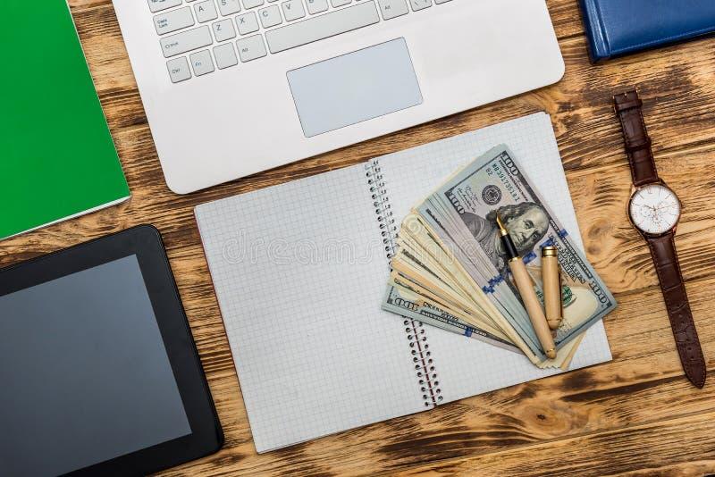 Bankbiljetten in dollar op pc-toetsenbord en leeg notepad stock foto's