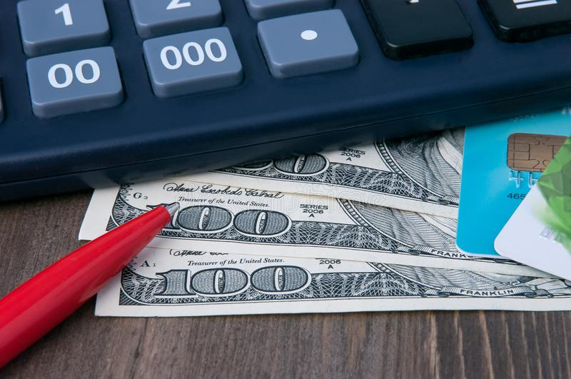 Bankbiljetten voor honderd dollars, creditcards, een calculator en een pen op een houten lijst stock afbeeldingen