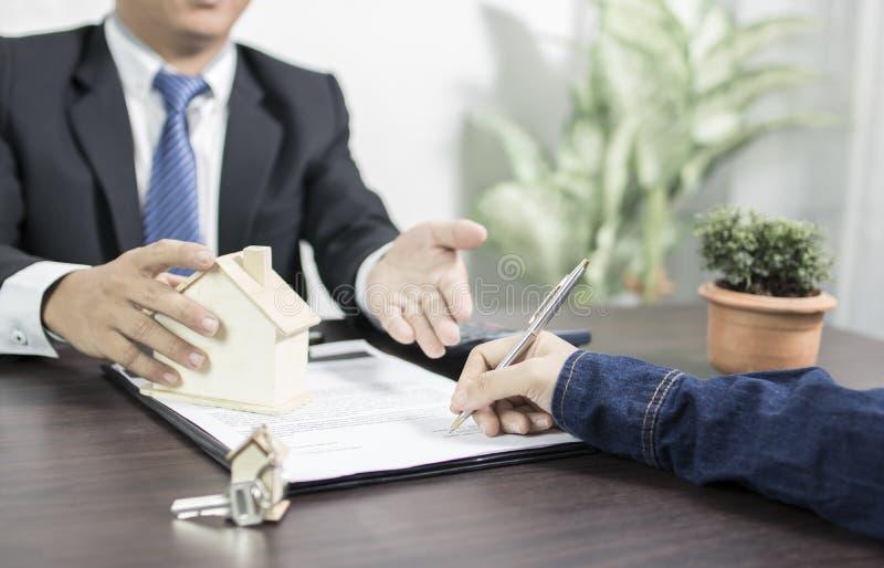 Bankbyrå som förklarar till den bostadslånfolk och köparen som undertecknar på royaltyfri bild