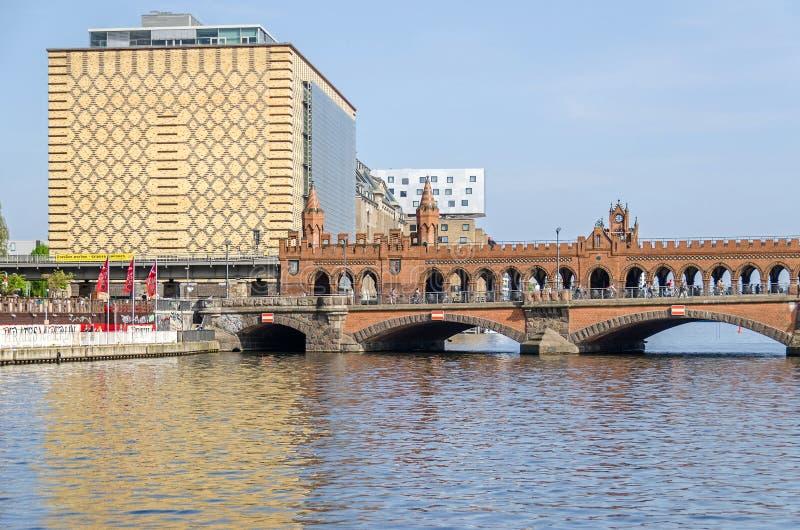 Banker av flodfesten med en del av den Oberbaum bron och byggnaden av Eierkuehlhaus i Berlin royaltyfri bild