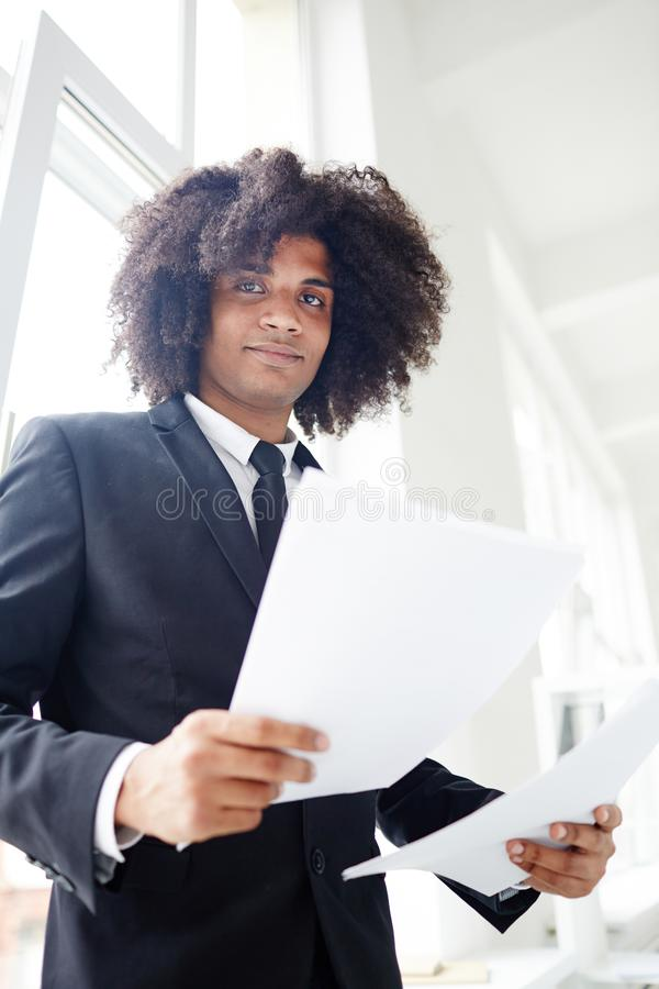 Banker with papers. Confident financier with papers standing by office window stock images