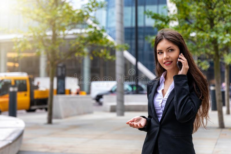 Banker woman talking on the mobile phone outside in the financial district. Attractive, confident banker woman outside in the financial district of London stock image
