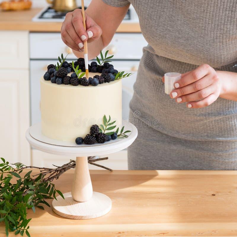Banketbakker die huwelijkscake met bessen verfraait Sluit omhoog Witte cake met roomkaas en verse bosbessen en braambessen stock afbeeldingen