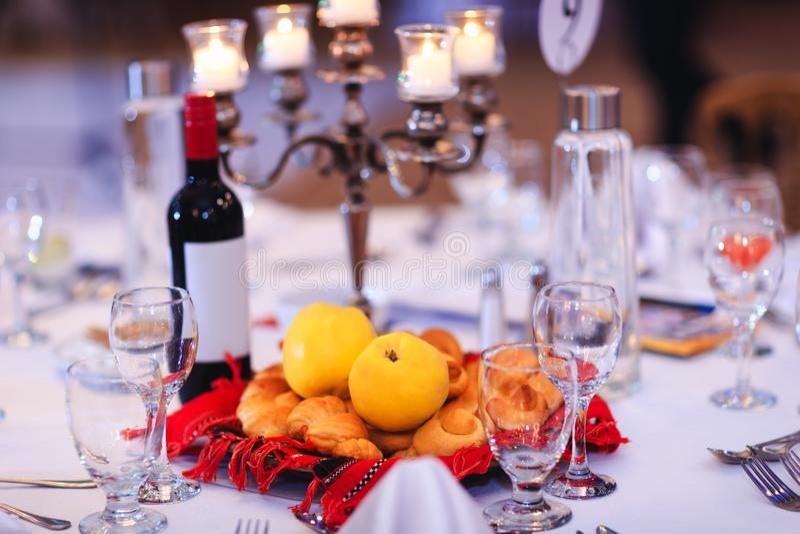 Banketttabell med gula kvitten, bullar eller kakor och flaska av vin som samlas i traditionell rumänsk handduk royaltyfri bild