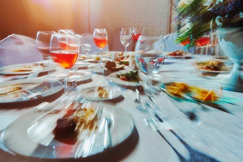 Banketttabell med mat, som han ser en berusad man, en alkoholist som drack många alkoholdrycker royaltyfri bild
