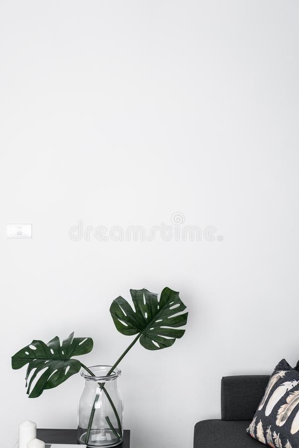 Bankhoek met kunstmatige installatie in glasvaas met lege witte geschilderde muur/ruimte voor reclame/binnenlandse marketing stock afbeeldingen
