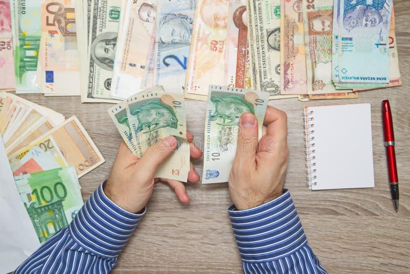 Bankier die Zuidafrikaans Geld tellen bij zijn bureaulijst, stock afbeeldingen