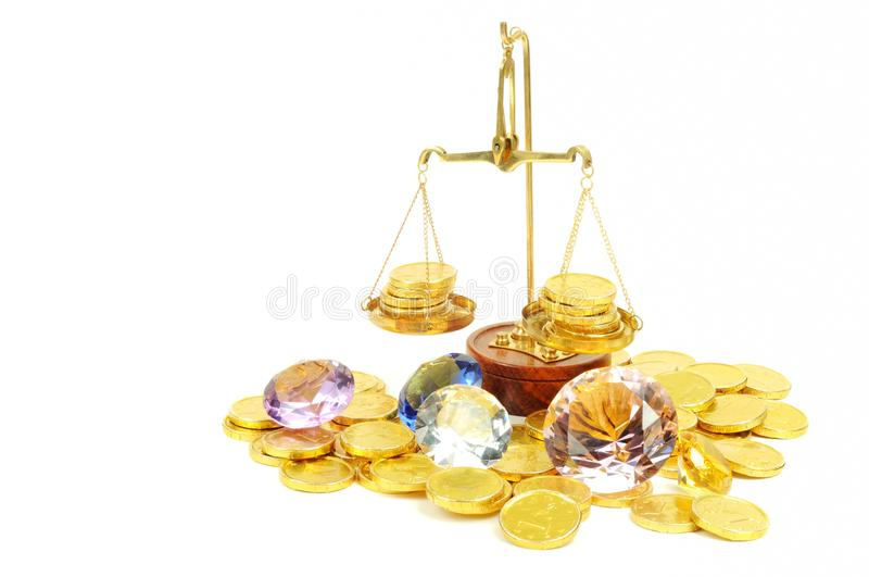 Banking. Gold coins of one euro and diamonds with scale, on white royalty free stock images