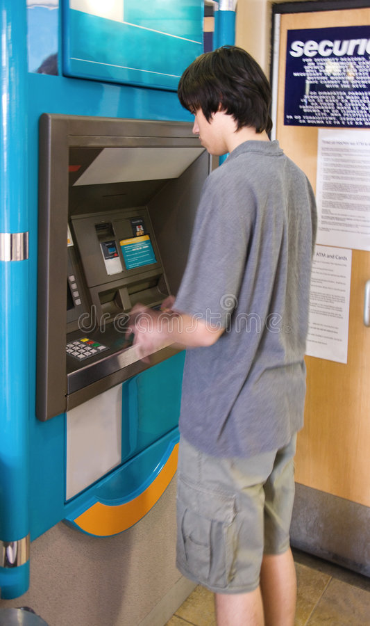 Banking. Young man withdrawing money from the ATM machine royalty free stock photo