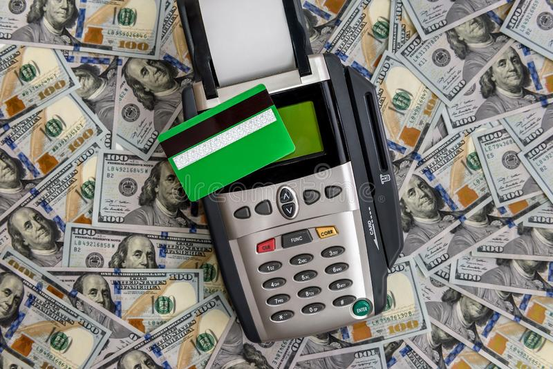 Banking terminal with green credit card and dollar background.  stock photos