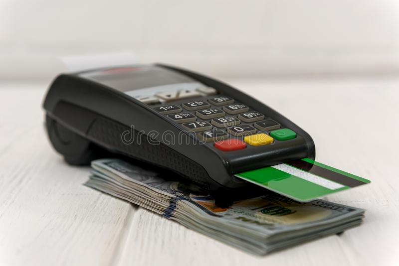 Banking terminal with green credit card and dollar background.  royalty free stock photo