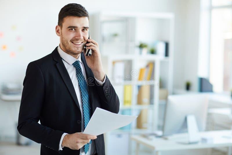 Bankir med telefonen och papper arkivfoton