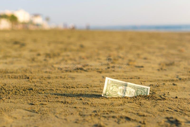 Banknot wartość jeden dolar w piasku na plaży Pojęcie tani wakacje i podróż obraz stock