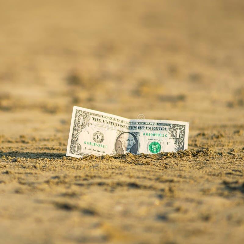 Banknot wartość jeden dolar w piasku na plaży Pojęcie tani wakacje i podróż zdjęcia stock