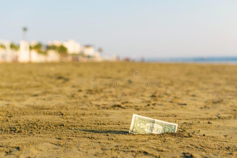 Banknot wartość jeden dolar w piasku na plaży Pojęcie tani wakacje i podróż obraz royalty free