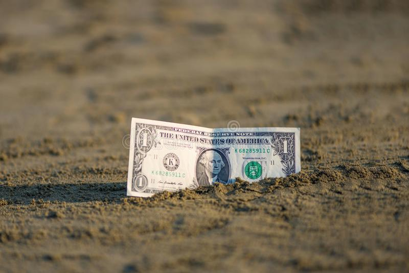 Banknot wartość jeden dolar w piasku na plaży Pojęcie tani wakacje i podróż zdjęcie stock