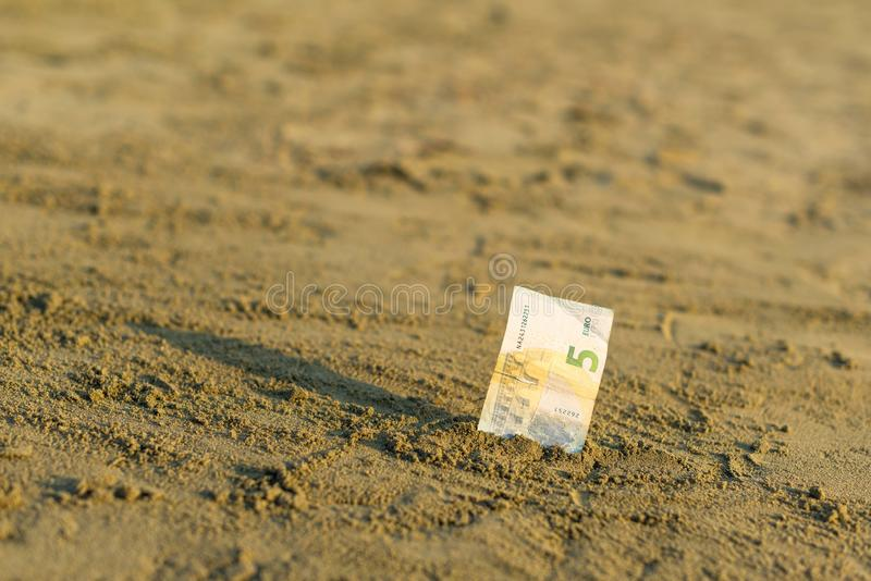 Banknot wartość pięć euro w piasku na plaży Pojęcie tani wakacje i podróż obraz royalty free