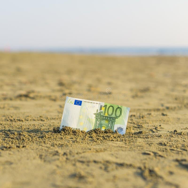 Banknot wartość sto euro w piasku na plaży Pojęcie tani wakacje i podróż obrazy stock
