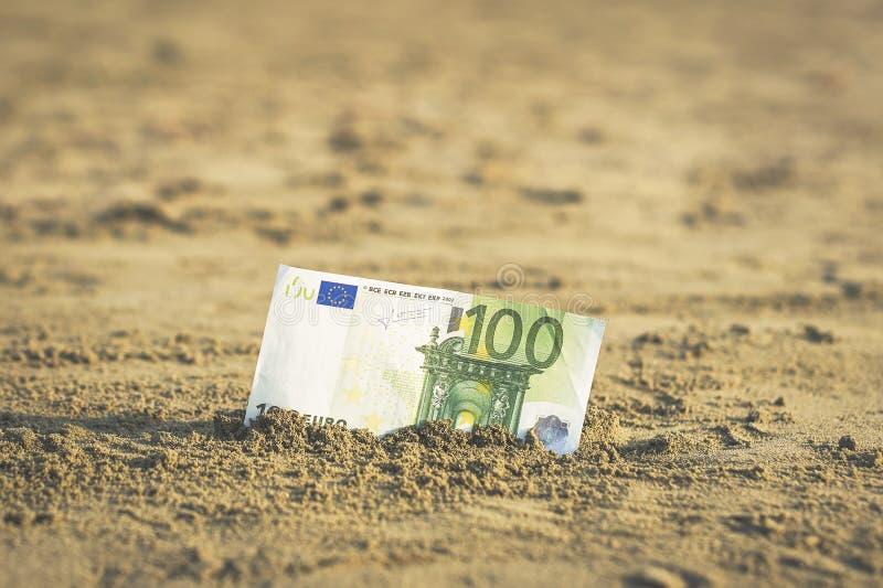 Banknot wartość sto euro w piasku na plaży Pojęcie tani wakacje i podróż obrazy royalty free