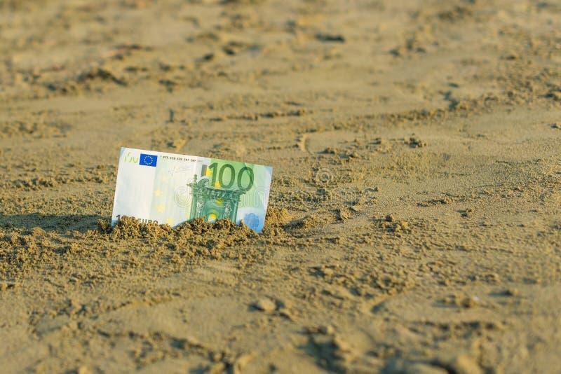 Banknot wartość sto euro w piasku na plaży Pojęcie tani wakacje i podróż obraz royalty free