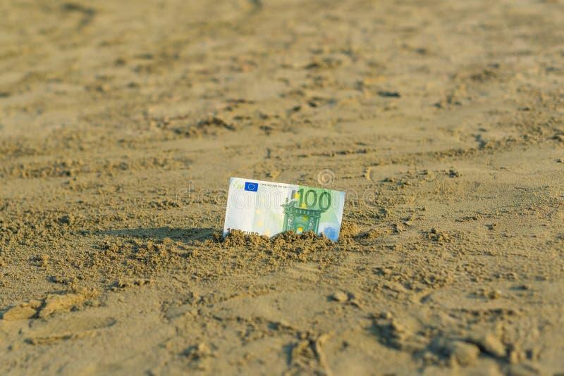 Banknot wartość sto euro w piasku na plaży Pojęcie tani wakacje i podróż fotografia stock