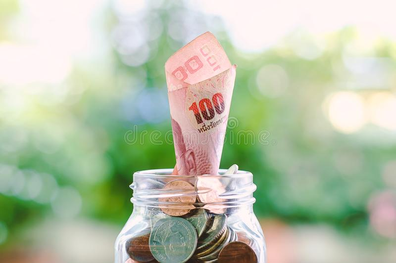 Banknote, 100 Baht Thai currency money growing from the glass jar of coins on blurred green natural background stock images