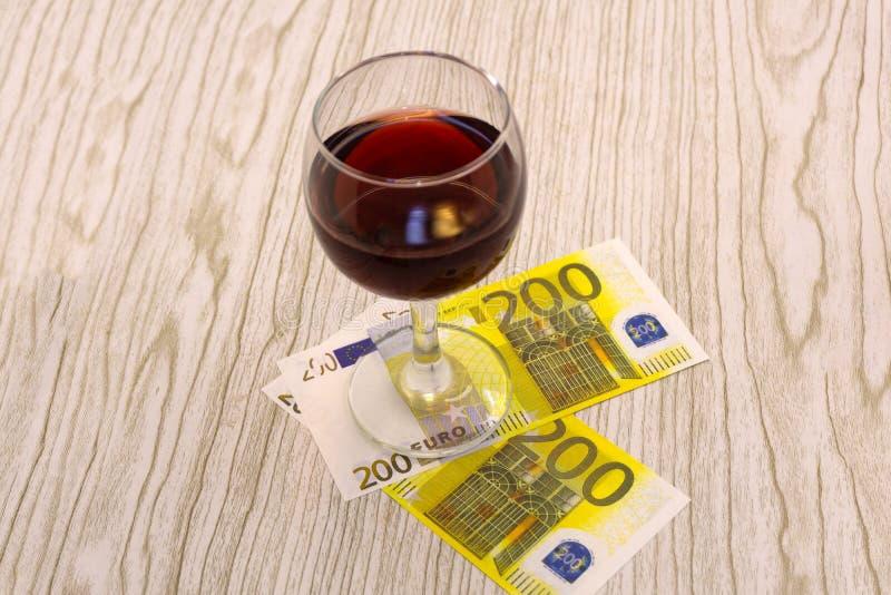 Banknote des Euros fünfzig innerhalb eines Weinglases über einem weißen Hintergrund stockbild
