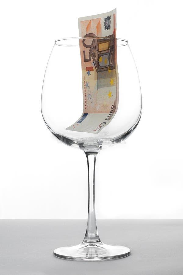 Banknote des Euros fünfzig innerhalb eines Weinglases stockbild