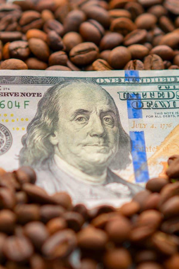 Banknote von 100 amerikanischen Dollar, zwischen Körnern des Kaffees Geschäftskonzept für den Kauf, den Verkauf, die Lieferung un stockbilder