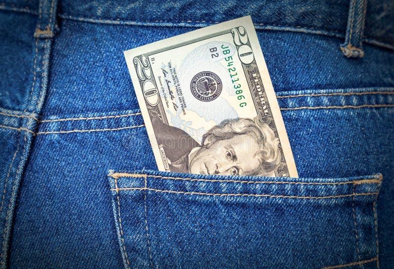 Banknote von zwanzig Dollar, die aus den Jeans heraus haften, stecken ein stockbilder
