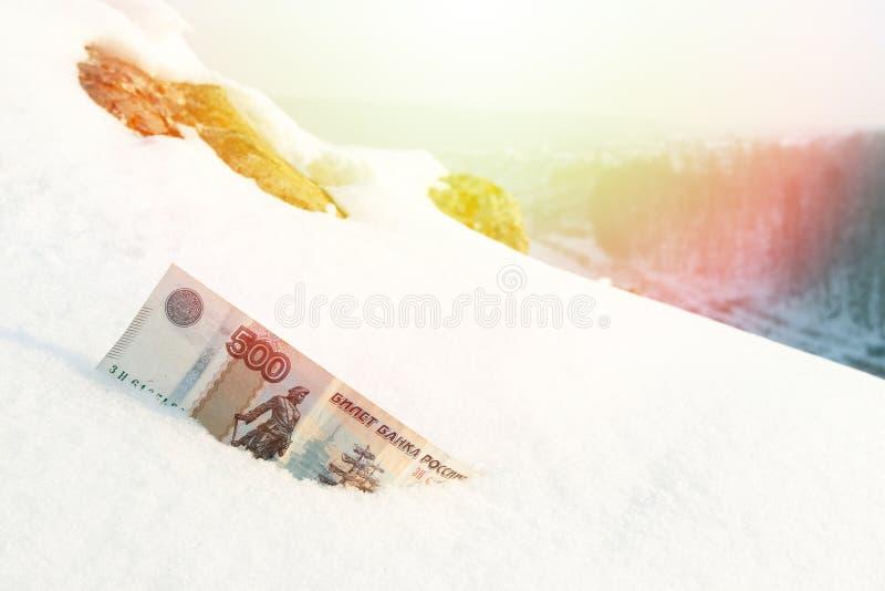 Banknote wert 500 Rubel im Schnee, im Sonnenlicht und im Wald lizenzfreies stockbild