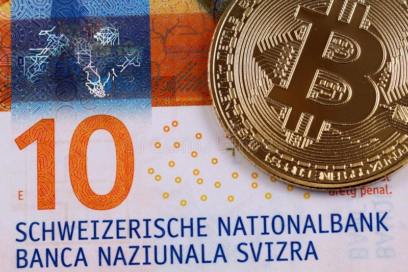 Banknote zehn Schweizer Franken mit einem goldenen bitcoin lizenzfreies stockbild
