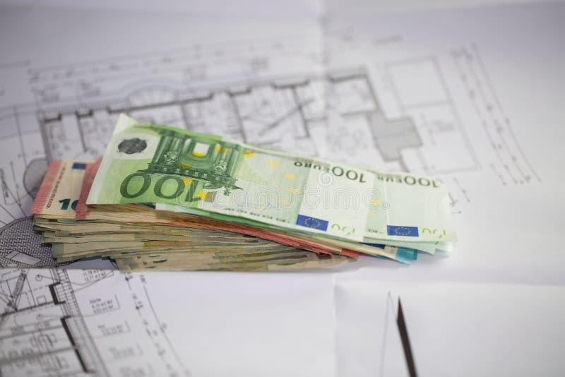 Banknoten, die auf Bauplänen liegen stockbilder