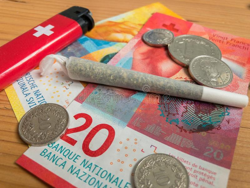 Banknoten, Feuerzeug und Gelenk des Schweizer Franken mit Marihuana stockbilder
