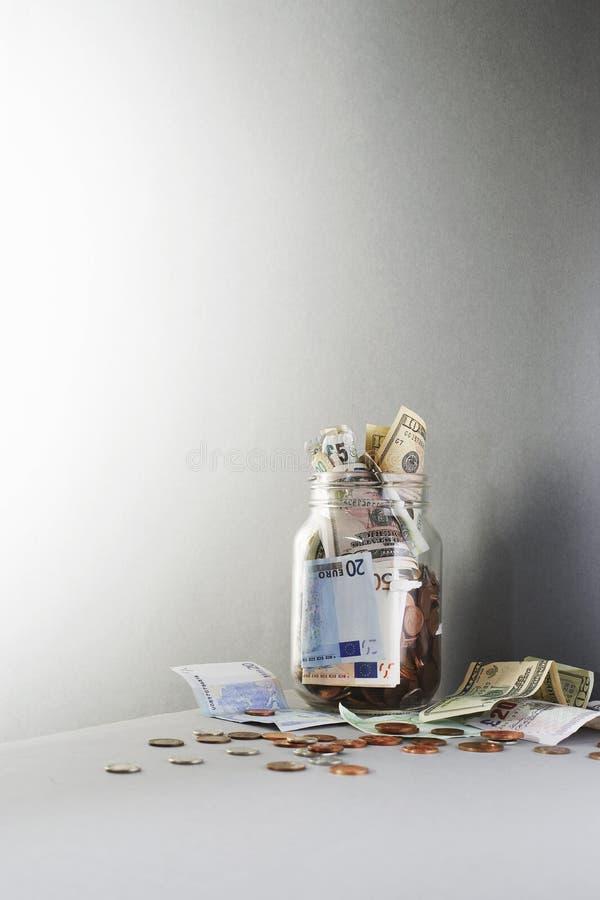Banknoten und Münzen, die vom Glas überlaufen stockfoto