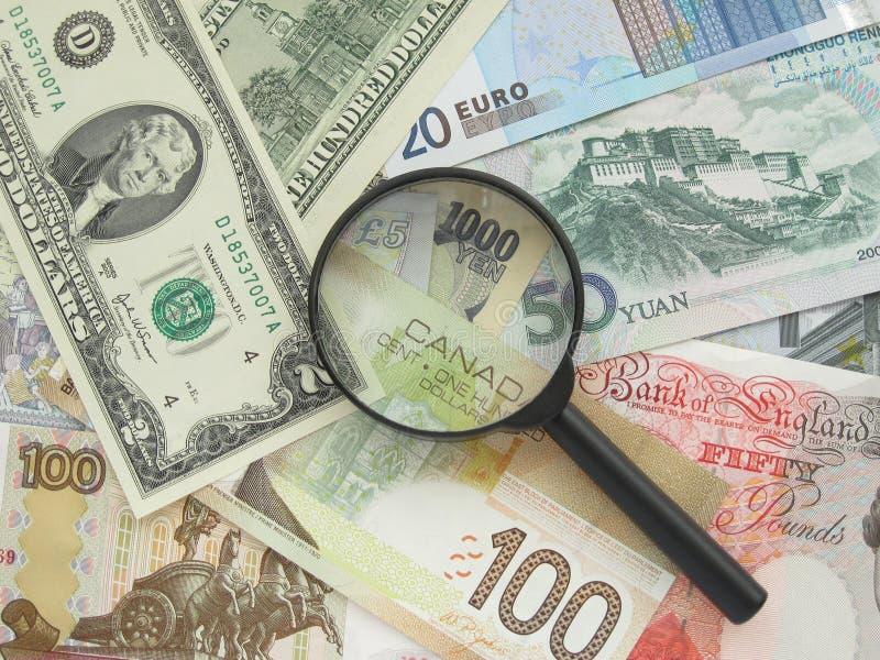 Banknoten und Vergrößerungsglas stockfotos