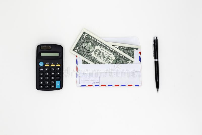 Banknotes in airmail envelope and black pen with calculator on white background. royalty free stock photo