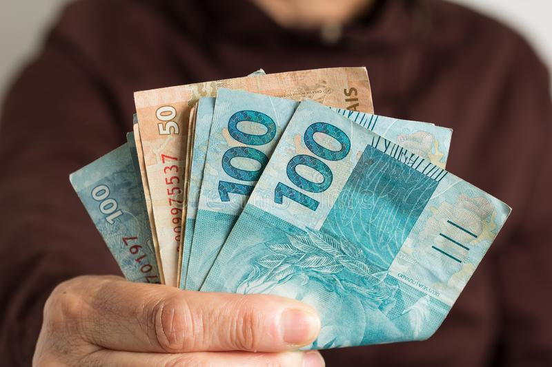 Banknotes of brazilian currency: Reais. Old retired person paying in cash. royalty free stock photo