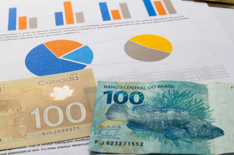 Banknotes of canadian currency: Dollar and brazilian Currency: R. Eal. Bills spread on paperwork reports analysis stock image