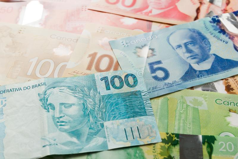 Banknotes of canadian currency: Dollar and brazilian Currency: R. Eal. Top view of bills spread and variation of amounts stock images