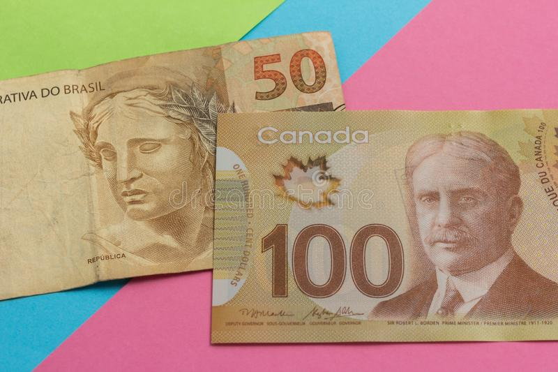 Banknotes of canadian currency: Dollar and brazilian Currency: Real. Bills on colorful bright table. Concept of loan, wealth royalty free stock photo