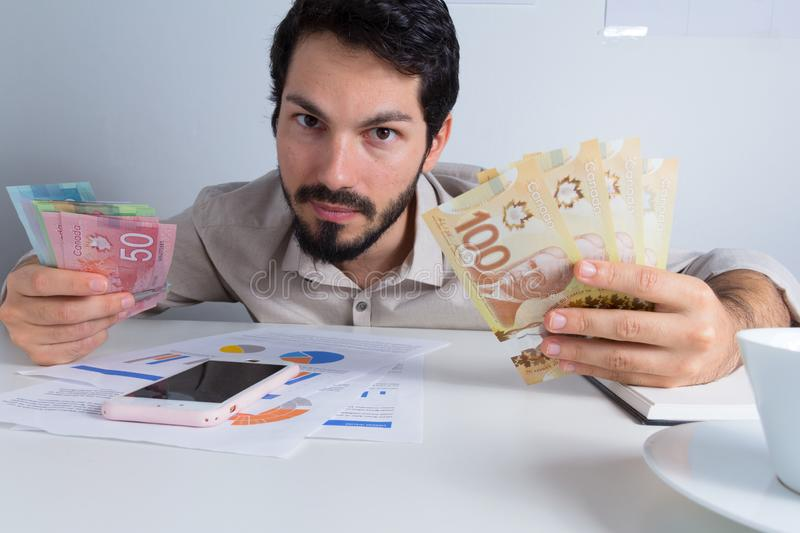 Banknotes of Canadian currency: Dollar. Business man offerign bills and looking at camera. Banknotes of Canadian currency: Dollar. Canada Money. Business man royalty free stock images