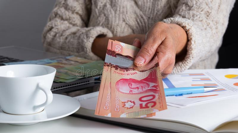Banknotes of Canadian currency: Dollar. Old woman offering bills. Banknotes of Canadian currency: Dollar. Canada Money. Old woman offering bills on table royalty free stock photo