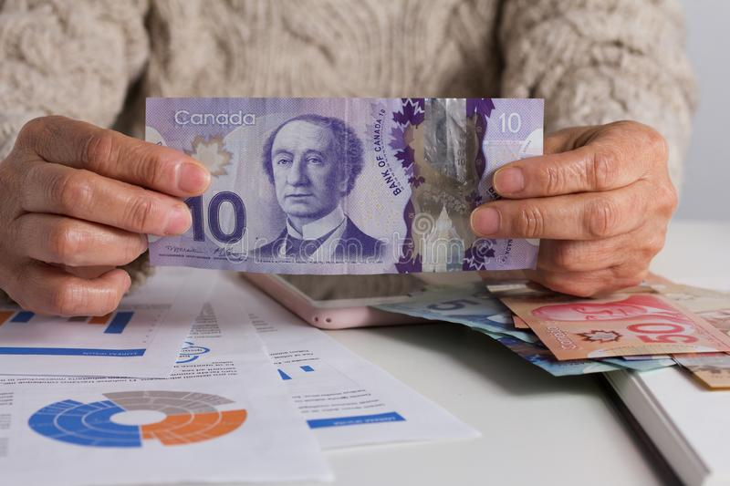 Banknotes of Canadian currency: Dollar. Person handling papernotes on desk. Banknotes of Canadian currency: Dollar. Canada Money. Person handling papernotes on royalty free stock photography