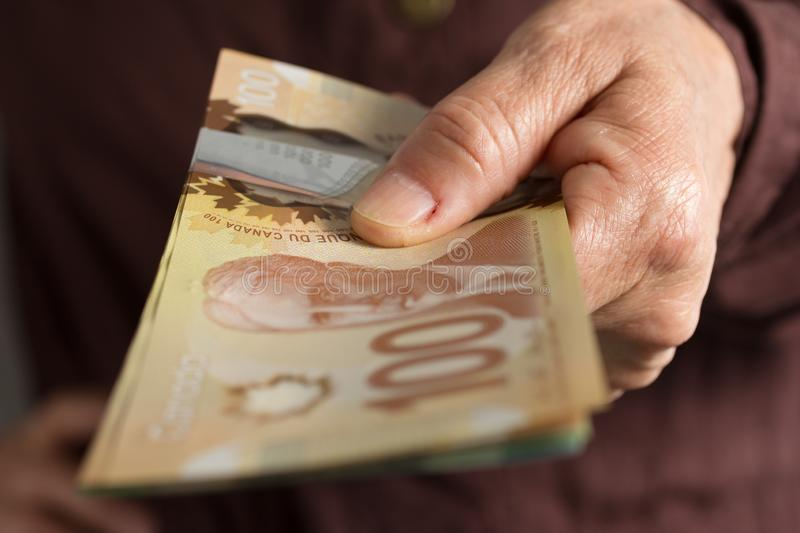 Banknotes of Canadian currency: Dollar. Front view senior person. Banknotes of Canadian currency: Dollar. Canada Money. Front view senior person holding bills stock photos