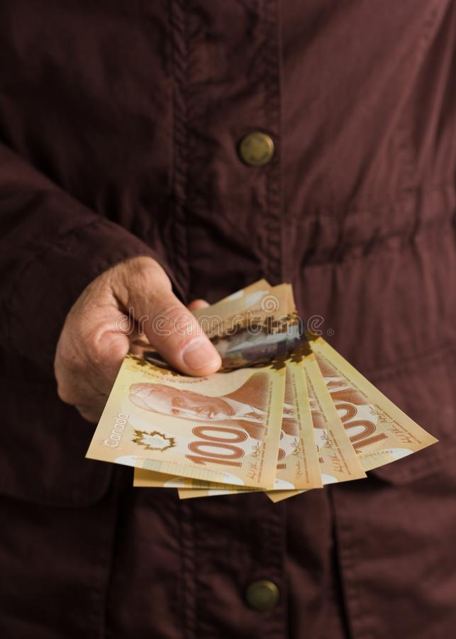Banknotes of Canadian currency: Dollar. Front view senior person holding bills. Banknotes of Canadian currency: Dollar. Canada Money. Front view senior person stock photography