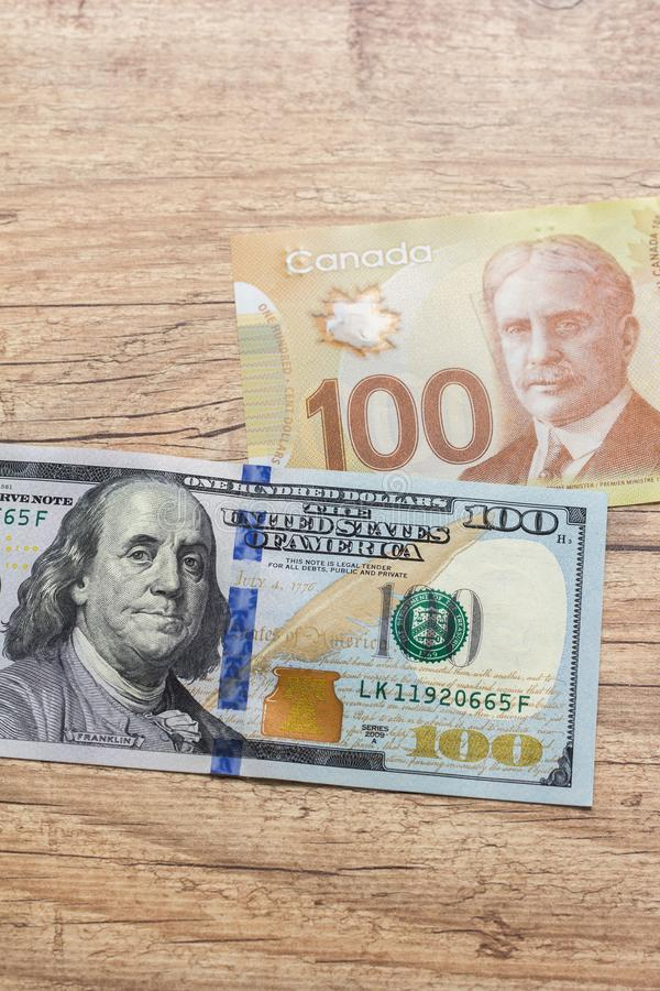 Banknotes of canadian currency: Dollar and North American Currency: US Dollars. Bils on wood rustic table. royalty free stock image