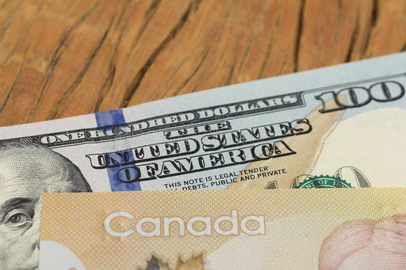 Banknotes of canadian currency: Dollar and North American Currency: US Dollars. Close up of cash bills on rustic wood table. Concept of loan, wealth royalty free stock images