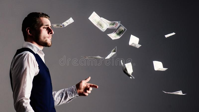 Banknotes, cash dollars fly in air around guy. Man in formal wear, businessman throwing money on grey background. Richness and wealth concept. Successful stock photo
